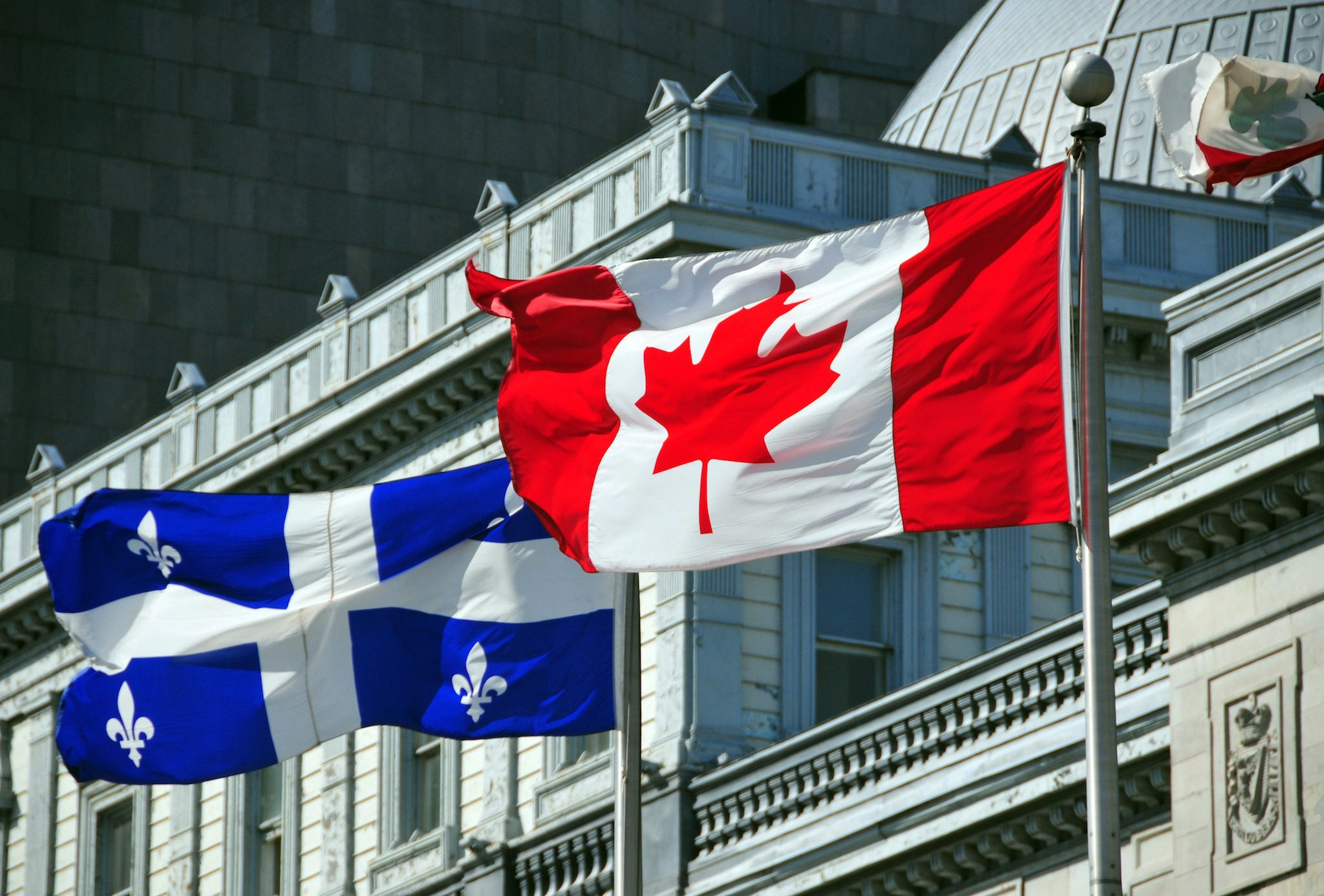 Montreal, Quebec, Canada: Canadian and Quebecer flags in front of the old Palace of Justice - Vieux palais de justice - Rue Notre Dame - Vieux-Montr?al - photo by M.Torres