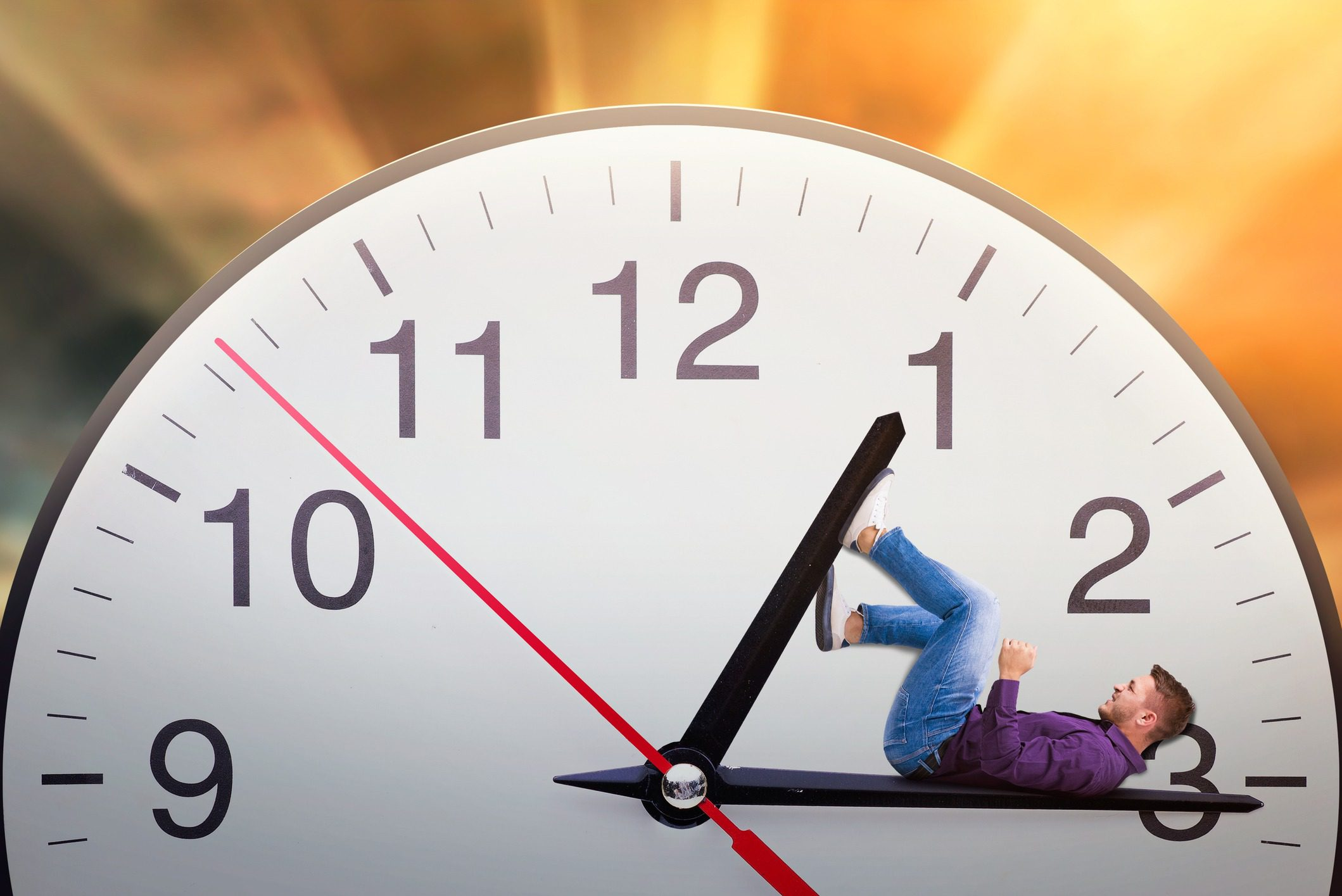 Man lies on the arrow of a huge clock and trying to stop time. Deadline concept