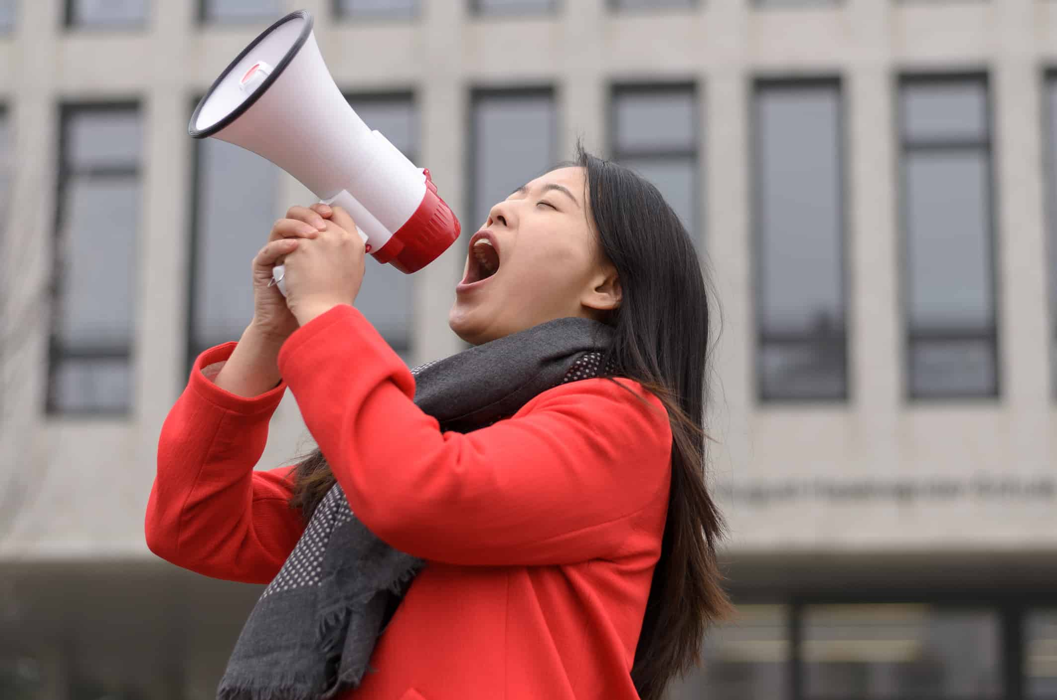 Asian woman in red coat shouting into megaphone.