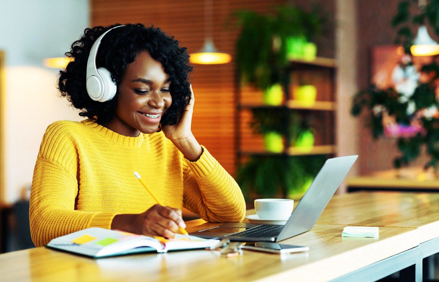 Black woman wearing headphones looking at laptop, smiling, and writing something down.