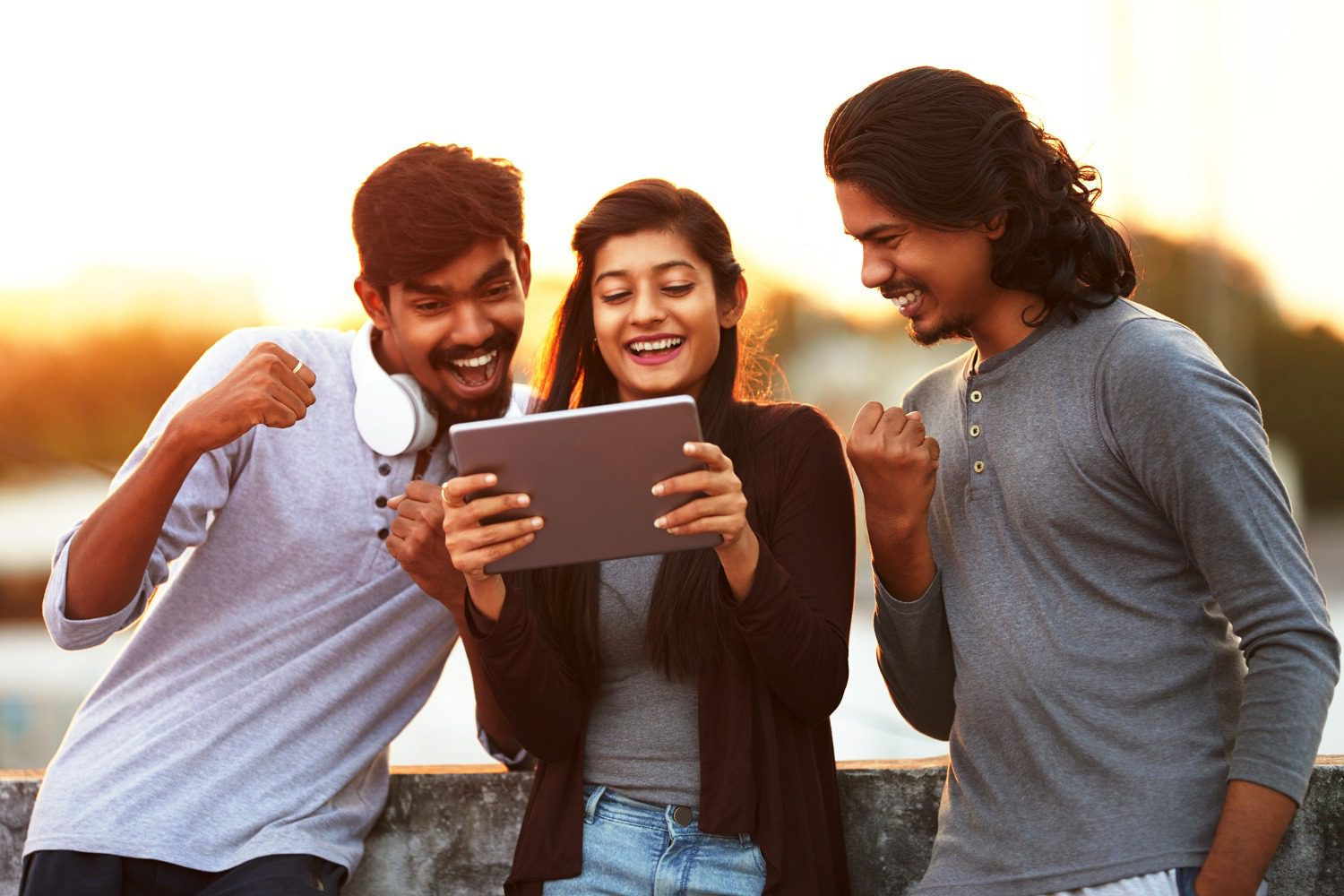 Three people smiling at a tablet.