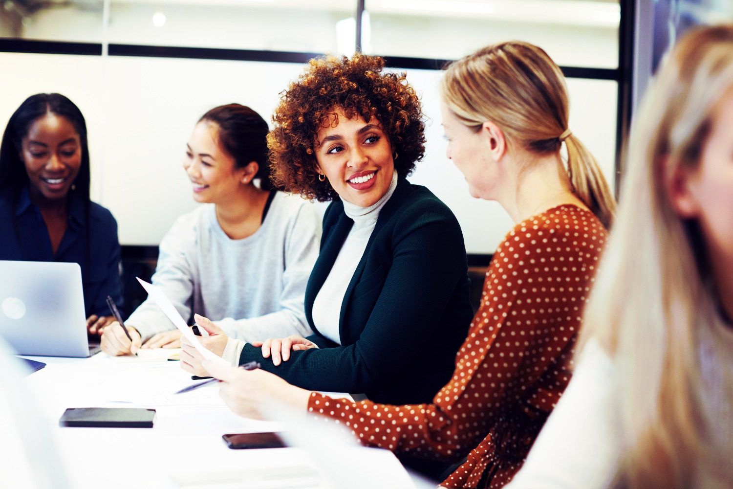 Women sitting around a desk at work - all talking and smiling. How can learning new languages help you and your career?